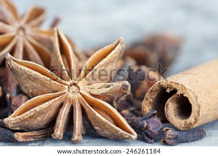 Anise star, cinnamon sticks, and cloves on old grey wood closeup - stock photo