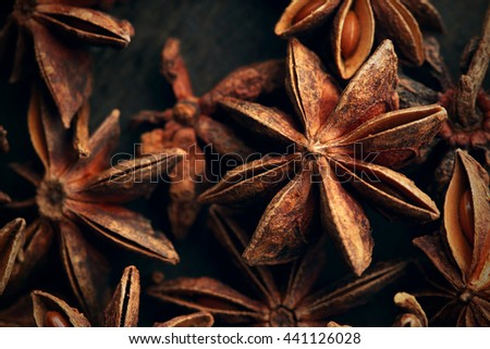 Anise star seeds on the wooden background. Aromatic ingredient in culinary, raw for alcohol drink arak, ouzo, raki, sambuca. Macro, close-up. Toned image. - stock photo