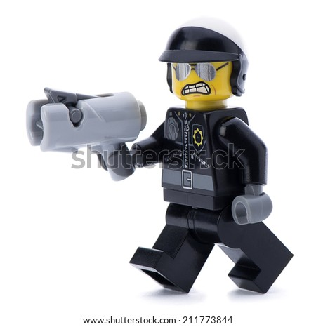 Ankara, Turkey - March 15, 2014 : Lego movie minifigure character bad cop with gun walking isolated on white background.  - stock photo