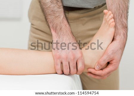 Ankle of a patient being manipulated in a room - stock photo