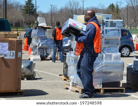ANN ARBOR, MI - APRIL 26:  A worker carries a printer past a pile of computers at an electronic recycling event in Ann Arbor, MI, April 26, 2014. - stock photo