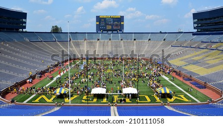 ANN ARBOR, MI - AUGUST 10:  Visitors meet players and others at Michigan stadium during Michigan Football Youth Day on August 10, 2014 in Ann Arbor, MI. - stock photo