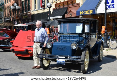 ANN ARBOR, MI - JULY 12: Owner Jack Beatty poses in front of his 1925 Detroit Electric at the Rolling Sculpture car show  July 12, 2013 in Ann Arbor, MI - stock photo