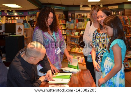 "ANN ARBOR, MI - JUNE 25: New York Times bestselling author Jim Ottaviani places his thumbprint on a book at a signing for his new book ""Primates"" at Nicola's Books June 25, 2013 in Ann Arbor, MI."