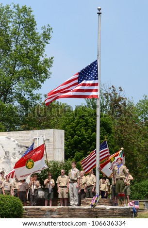 ANN ARBOR, MI - MAY 27: Boy scouts after placing the flag at half mast at the annual Memorial Day observance on May 27, 2012 at Arborcrest Memorial Park in Ann Arbor, MI - stock photo