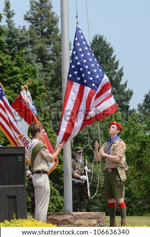 ANN ARBOR, MI - MAY 27: Unidentified boy scouts raise the flag at the Memorial Day observance on May 27, 2012 at Arborcrest Memorial Park in Ann Arbor, MI - stock photo