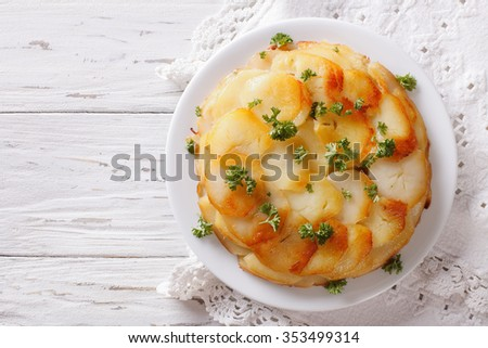 Anna potatoes with butter on a plate closeup. Horizontal  top view
