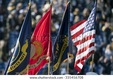ANNAPOLIS, MD - OCTOBER 31: The US Navy, Marine Corps, Brigade of Midshipmen flags fly next to the US flag on the field prior to the AAC football game October 31, 2015 in Annapolis, MD.  - stock photo