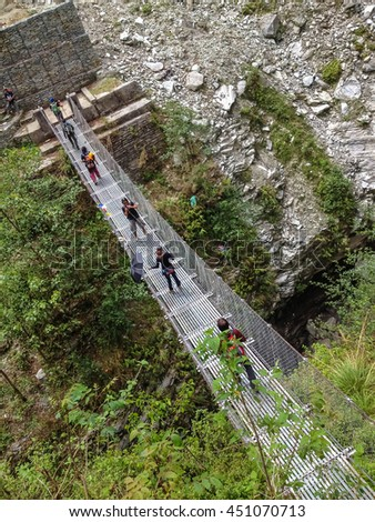 ANNAPURNA, NEPAL - APRIL 14, 2012 : Trekker walk across bridge on the way to Annapurna Base Camp, Nepal