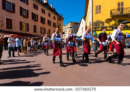 ANNECY, FRANCE - AUGUST 25, 2010: Apron wearing professional waiters with loaded trays run around old Annecy during the Waiter's Race on August 25, 2010 in Annecy, France. Horizontal - stock photo