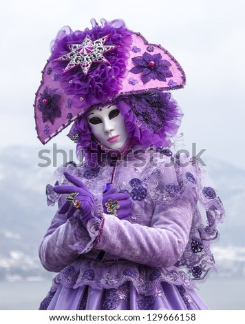 ANNECY, FRANCE, FEB 23:Unidentified person disguised in a violet costume in Annecy, France,on February 23, 2013.Every year in Annecy is held a Venetian Carnival to celebrate the beauty of real Venice.