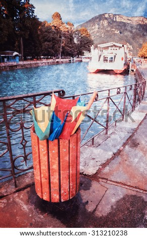 Annecy lake after rain. Broken colorful umbrella in garbage can. Tourist boat and mountains at background. Retro aged grungy photo with scratches. - stock photo