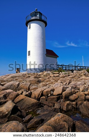 Annisquam lighthouse guides mariners around the rocky coastline of the Massachusetts North Shore. - stock photo