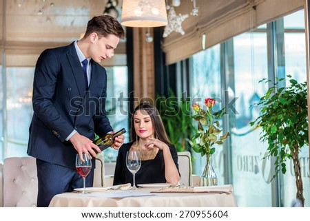 Anniversary Celebration at the restaurant. Romantic dinner in the restaurant. Young loving couple visiting the restaurant while her husband was poured into a glass of wine - stock photo