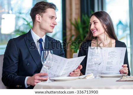 Anniversary Celebration at the restaurant. Romantic dinner in the restaurant. Young loving couple while visiting a restaurant menu holds in her hands and smiling at each other - stock photo