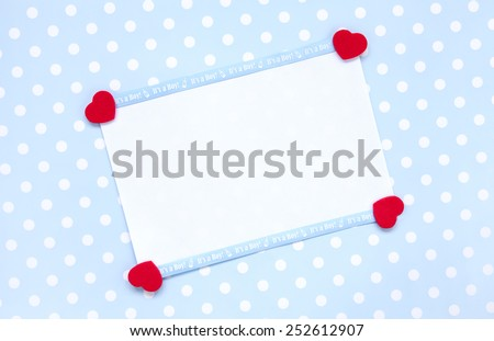 Announcement or invitation. Blank note paper with Its a boy baby blue ribbon, and four red heart shapes on a blue polka dot background.