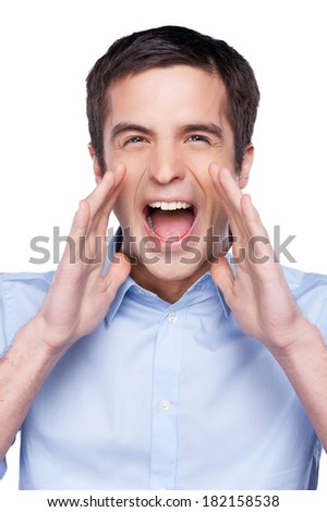 Announcing good news. Handsome young man in blue shirt at camera and shouting while standing isolated on white - stock photo