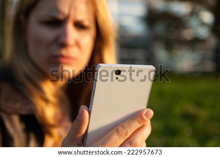 annoyd woman with smartphone in sunlight