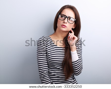 Annoyed angry young woman in eyeglasses thinking and looking up on blue background