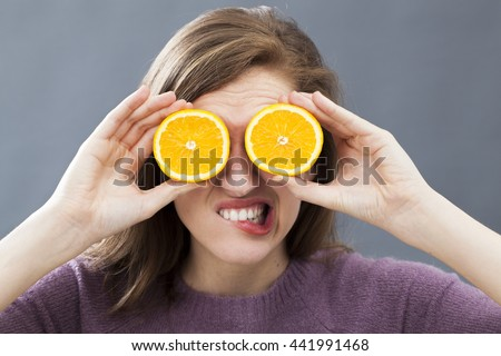 annoyed beautiful young woman biting her lips, disliking holding two orange slices on her eyes as fun colorful glasses, indoors