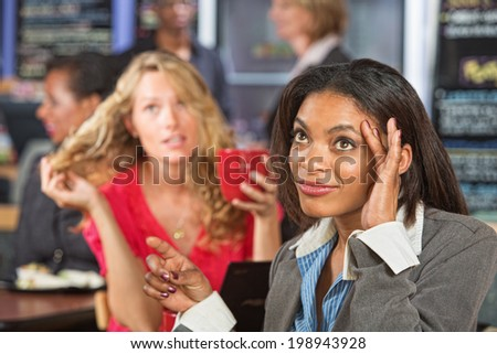 Annoyed Black woman talking with emotional friend - stock photo