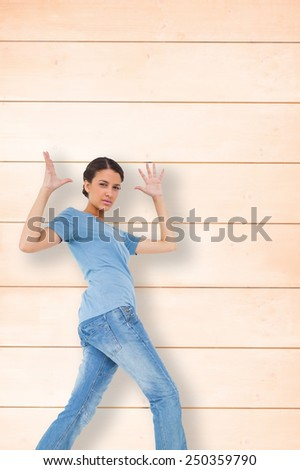 Annoyed brunette gesturing against wooden background in pale wood - stock photo