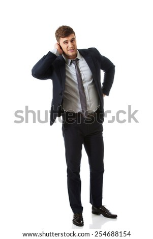 Annoyed businessman covering his painful ear. - stock photo
