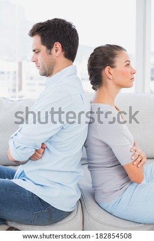 Annoyed couple sitting back to back on the couch at home in the living room - stock photo