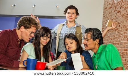Annoyed female cafe waitress among confused customers - stock photo