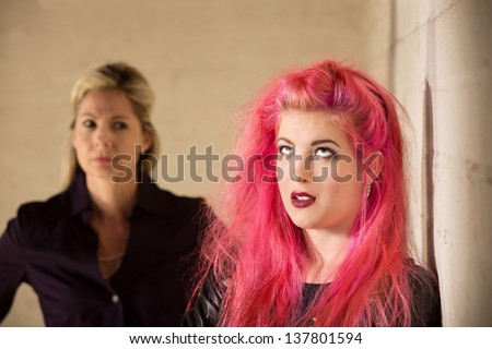 Annoyed girl in pink hair with upset parent - stock photo