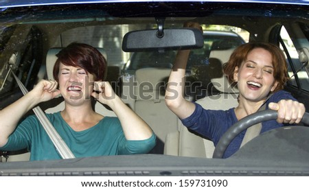 annoyed passenger and singing female driver - stock photo