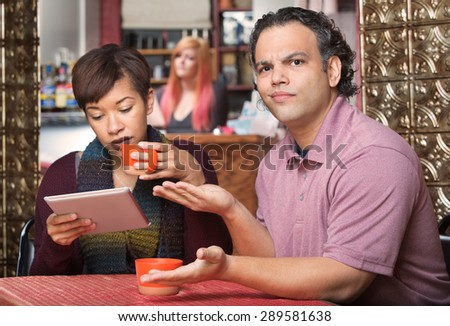 Annoyed spouse sitting with wife reading tablet computer - stock photo