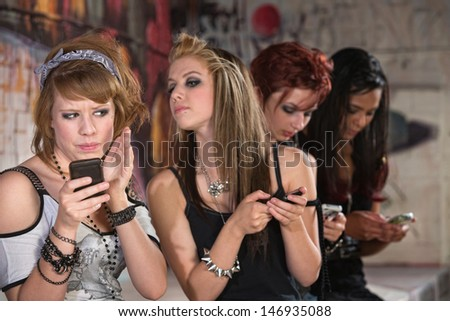 Annoyed teenager hiding phone from nosey girl - stock photo