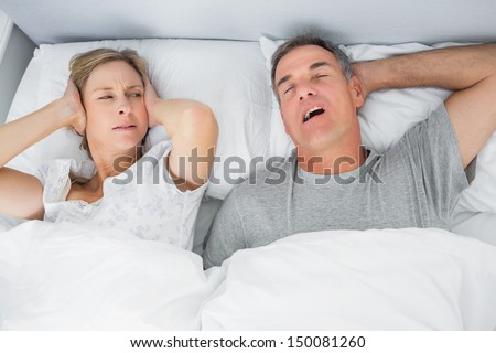 Annoyed wife blocking her ears from noise of husband snoring in bedroom at home - stock photo