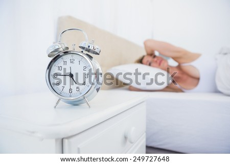 Annoyed woman covering her ears from alarm clock noise in bed at home in the bedroom - stock photo