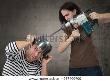Annoyed woman drilling into her boyfriend's head - stock photo