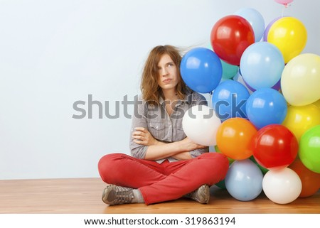Annoyed Woman Holding Balloons - stock photo