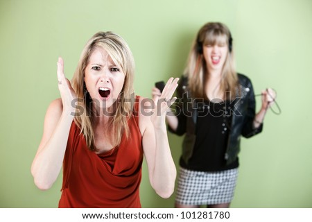 Annoyed woman in front with noisy girl with headphones - stock photo