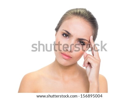 Annoyed young brunette woman looking at camera on white background - stock photo