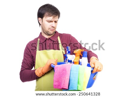 Annoyed  young man with apron and cleaning equipment over white background - stock photo