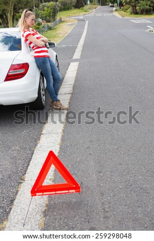 Annoyed young woman beside her broken down car in the street - stock photo