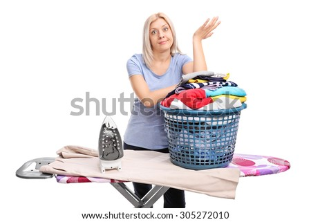 Annoyed young woman standing behind an ironing board and gesturing with her hand isolated on white background - stock photo