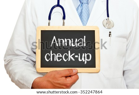 Annual check-up - doctor holding chalkboard with text on white background - stock photo