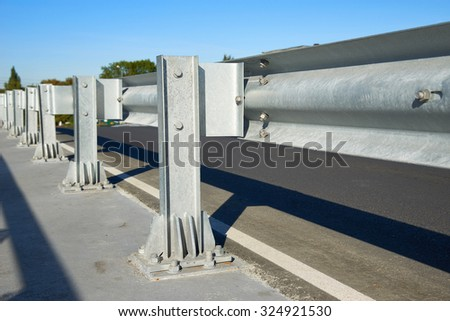Anodized safety steel barrier on freeway bridge - stock photo