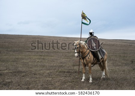 Anonymous ancient sarmatian horseman with spear in steppe - stock photo