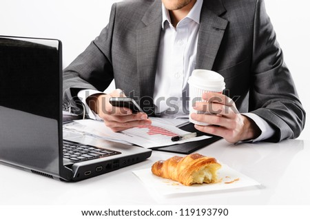 Anonymous business man types on smartphone while having a coffee and snack at his desk with laptop computer and documents - stock photo