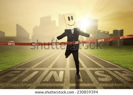 Anonymous business person wearing cardboard head and win a competition in 2015 - stock photo