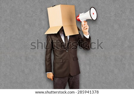 Anonymous businessman holding a megaphone against grey background