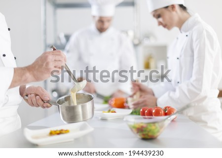 anonymous hands preparing food in professional kitchen - stock photo