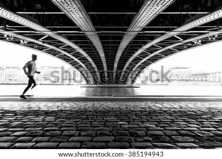 Anonymous male athlete running under a bridge in Lyon on a cold winter day. Sports concept with motion blur and shallow focus.